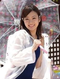 Kana Yuuki in bathsuit plays with umbrella in the balcony